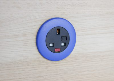 Pip in light wood with dark blue bezel and black UK fused socket