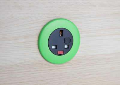 Pip in light wood with green bezel and black UK fused socket