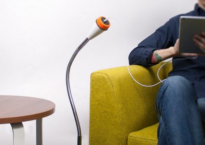 pose, silver with white and orange bezel freestanding power next to a green sofa with a man using an ipad