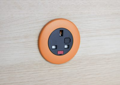 Pip in light wood with orange bezel and black UK fused socket