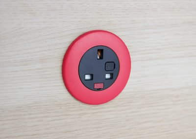 Pip in light wood with red bezel and black UK fused socket