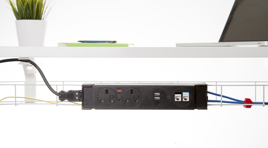 black underdesk power module in white cable tray under a desk