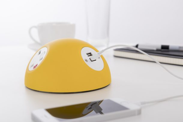 Yellow Pluto desktop module with UK fused power sockets and TUF USB charger. On a desk next to a notebook, cup of coffee and iphone
